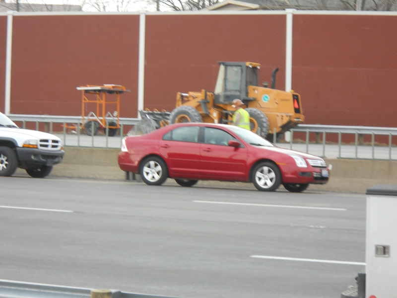 red car and yellow construction vehicle moving along on a highway at a crash scene
