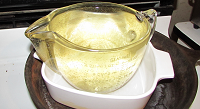 picture of golden colloidal silver in a glass jar on nancy gurish's stove