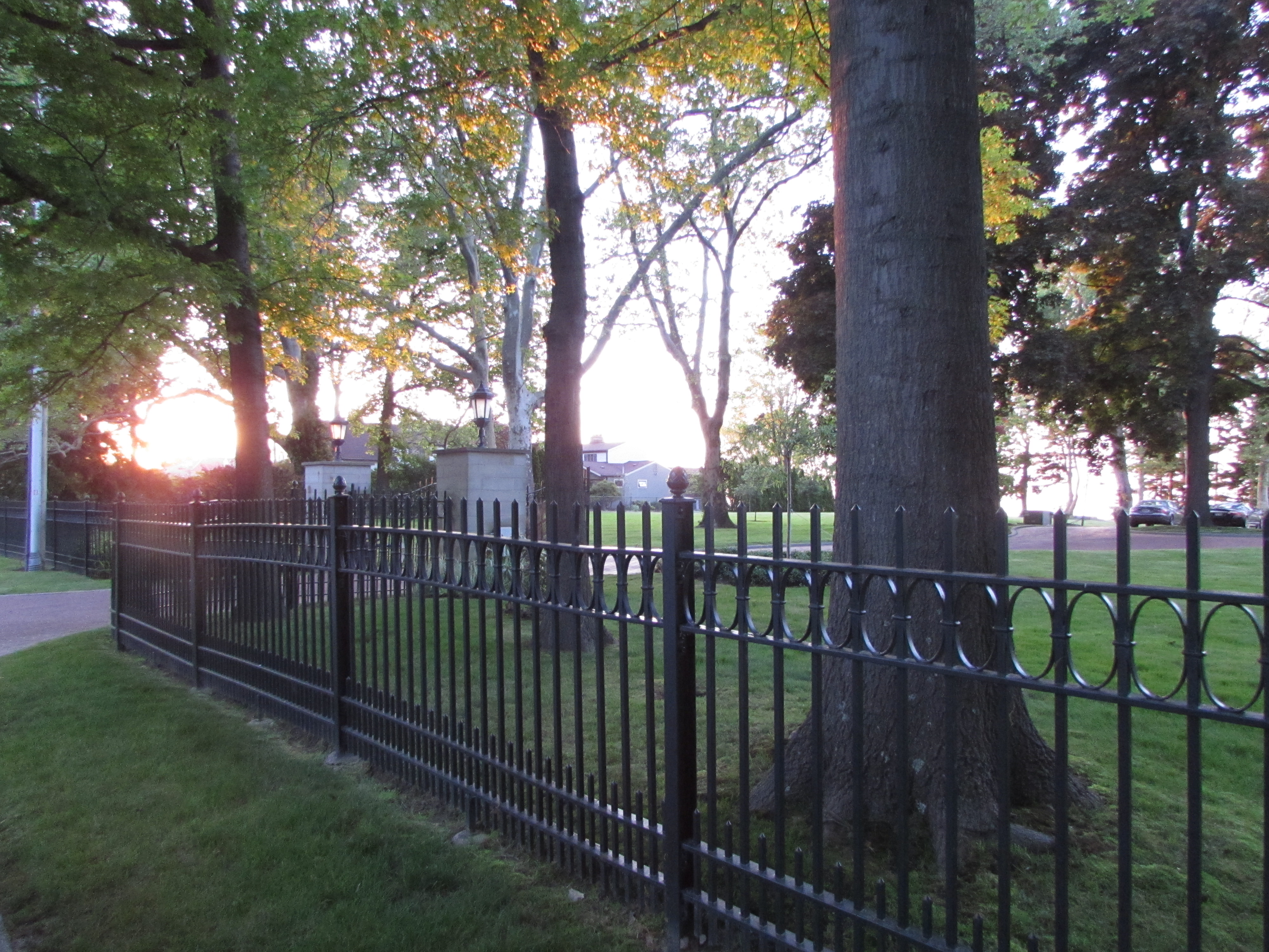 black wrought iron fence five foot high with trees and sunset on lake erie in usa