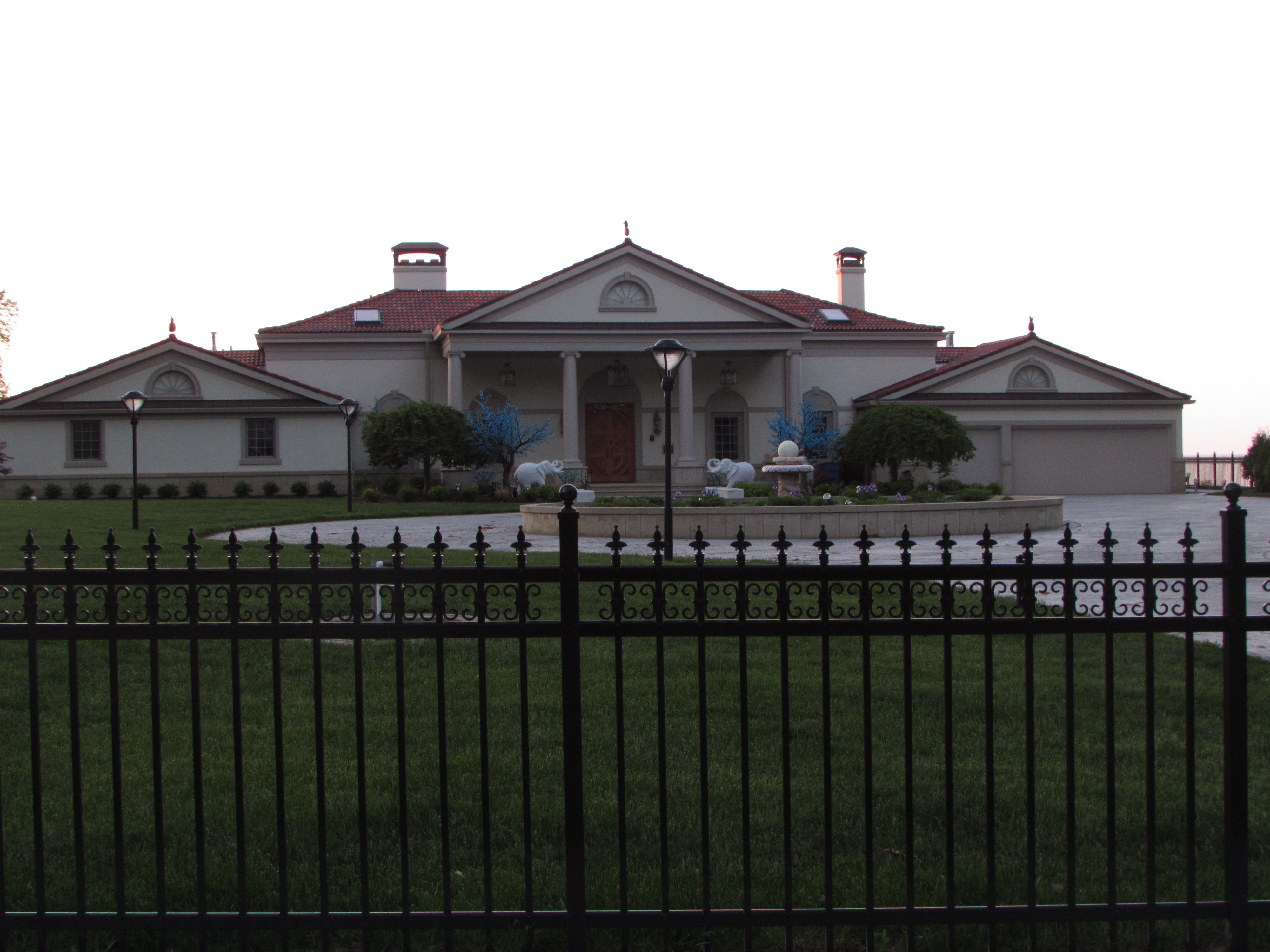 front lawn with black wrought iron rail in front and home in the back ground beautiful home on lake front lake erie in northern ohio usa, image taken by Nancy K Gurish, Editor Your Health And Tech Friend Magazine, A Julialanan Production LLC,